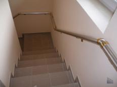 Фотография пристенного поручня из анодированного алюминия с креплениями «под золото» на лестнице