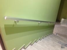 Фото пристенного поручня из анодированного алюминия на стене светло-зеленого цвета
